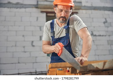 Front view of a focused joiner in safety goggles cutting off a piece of wood