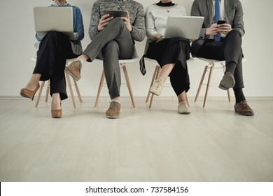 Front view of four people using new technology while sitting on chairs in waiting room