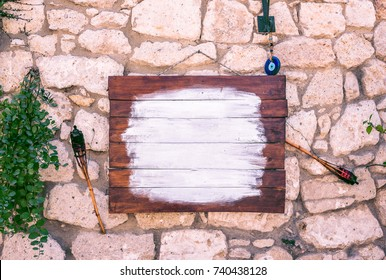 Front view of free and clean brown wooden signage board on a white ancient stone wall with hanging plants and evil eye bead for decoration.There is a copy space for editing.