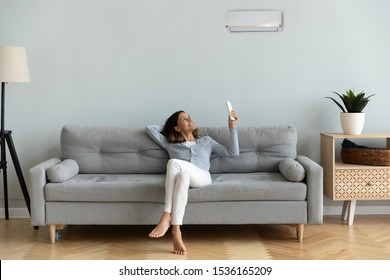 Front view full length joyful young mixed race woman relaxing on cozy couch in living room, holding remote controller, turning on cooler system air conditioner, setting comfortable temperature.