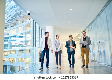 Front view full length portrait of four young successful business people walking confidently down glass balcony in modern office building, copy space