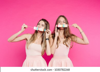 Front view of funny and beautiful girls like dolls having fun with marshmallow candies on stick and hiding lips and mouth. Pretty positivity sisters after party holding candies and looking at camera.