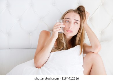 Front view of a girl with tousled hair hold glass water, suffering head ache sitting on bed in the living room at home.Woman hangover,healthcare concept