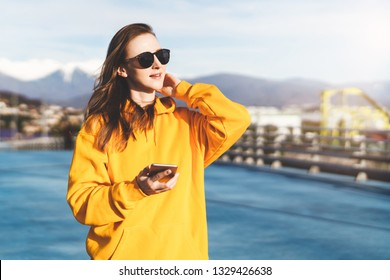 Front view. Girl in yellow hoodie and sunglasses holding smartphone while standing outdoors. Woman traveler has adventure trip.Tourist uses app for travelers on mobile phone. In background mountains.