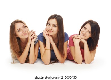 Front view of girls friends lying smiling on floor looking at camera, over white background