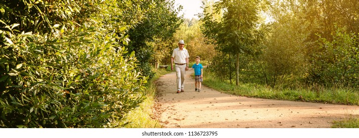 Front view of grandfather with hat and grandchild walking on a nature path