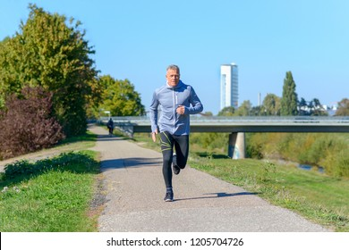Front view of gray man wearing sportswear running along river