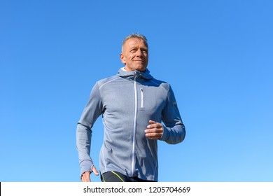 Front view of gray smiling man wearing sportswear running along river in a low angle view