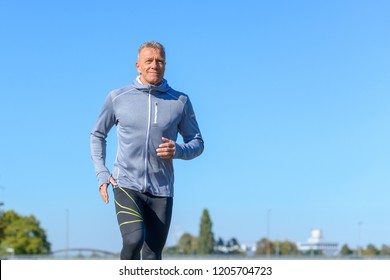 Front view of gray smiling man wearing sportswear running along river in a close up view