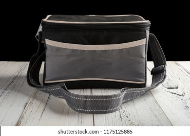 front view grey and black lunch pack carrier on a wood table on black background