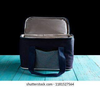 front view grey and blue lunch pack carrier with the top opened on a wood table on black background