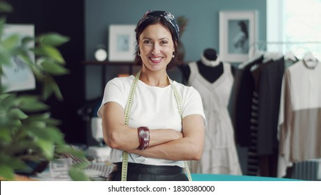 Front view of grinning female dressmaker with arms crossed standing in sewing workshop looking at camera