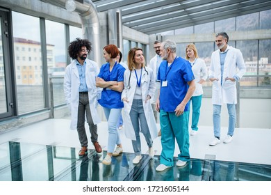 Front view of group of doctors walking in corridor on conference.