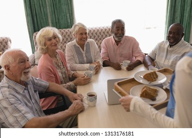 Front view of group of happy senior people having black coffee with cake in living room at nursing home