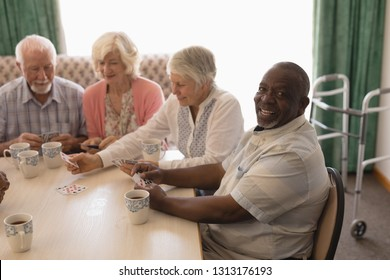 Front view of group of happy senior people playing cards in living room at nursing home