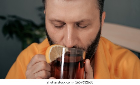 Front view guy is drinking black tea. Attractive young man is ill and drinks tea with lemon while sitting in bed. Cold, flu, sore throat, runny nose, acute respiratory disease concept. Close-up