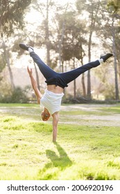 Front view of a gymnastic man handstand on one hand doing acrobatic posture