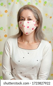 Front view half body portrait of middle aged mixed race woman wearing DIY fabric face mask for protection against coronavirus (COVID-19) and other infectious diseases. Looking forward.