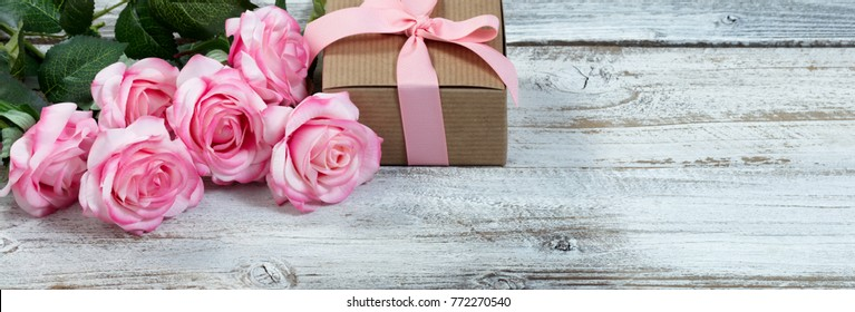 Front view of a half a dozen pink roses and gift box on rustic white wood in flat lay view