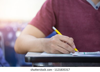front view hand high school or university student in casual holding pencil writing on paper answer sheet.sitting on lecture chair taking final exam or study attending in examination room or classroom