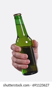 Front view from a hand hold a green beer bottle isolated on white background.