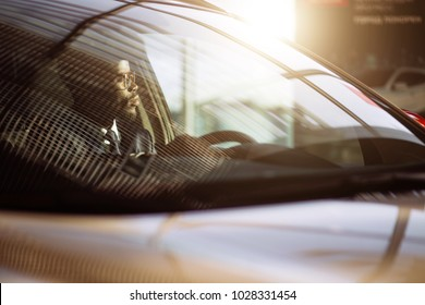 front view of Handsome african elegant serious man drives a car
