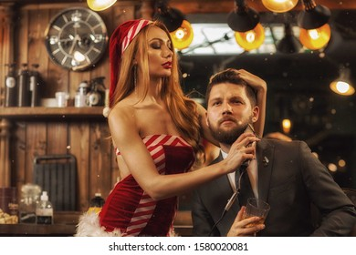 Front view of handsome bearded man in smart suit sitting in barbershop while sexy female in santa claus costume shaving him. Attractive stylist in process of working. Concept of new year servicing.