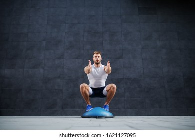 Front view of handsome caucasian muscular bearded man doing squat exercise on bosu ball. In background is gray wall.