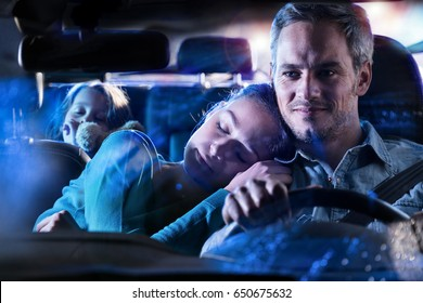 Front view. Handsome man driving his car at night, his wife fell asleep on his shoulder. At the back, his little girl fell asleep with her teddy in her arms