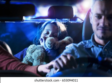 Front view. Handsome man driving his car at night. At the back, his little girl fell asleep with her teddy in her arms