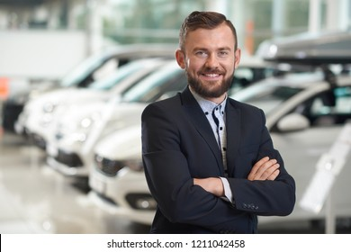 Front view of handsome man standing in modern car center and posing. Bearded manager wearing in dark blue jacket smiling and looking at camera. Row of automobiles on background.