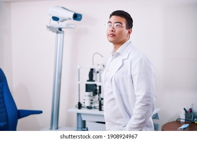Front view of a handsome thoughtful young Latin American eye doctor wearing a lab coat