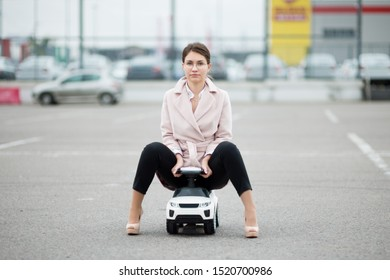 front view of a handsome young woman sitting in a child car in a parking lot, front view