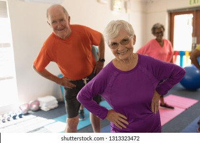 Front view of happy active senior couple exercising in fitness studio