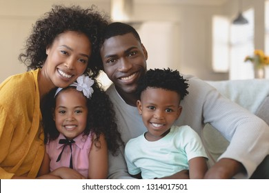 Front view of happy African American family sitting on sofa and looking at camera in a comfortable home