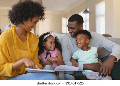 Front view of happy African American parents with their cute children reading storybook on the sofa in a comfortable home