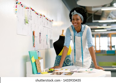Front view of happy African american female graphic designer leaning on table in office