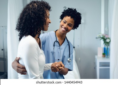 Front view of happy African American female doctor helping female patient to walk in the ward at hospital