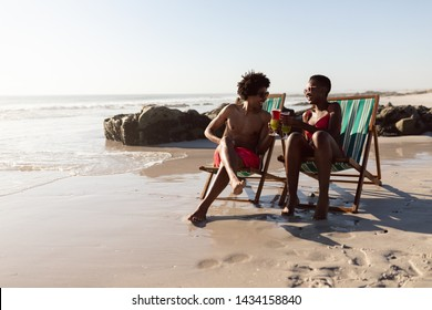 Front view of happy African-american couple toasting glasses of cocktail while relaxing in a beach chair on the beach