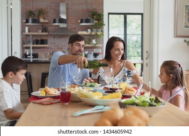 Front view of happy Caucasian family having food and champagne on dining table at home. Social distancing and self isolation in quarantine lockdown for Coronavirus Covid19