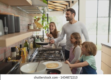 Front view of happy Caucasian family preparing food in kitchen in a comfortable home. Social distancing and self isolation in quarantine lockdown for Coronavirus Covid19