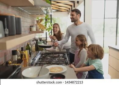 Front-View glückliche kaukasische Familie bereiten Essen in der Küche in einem komfortablen Haus