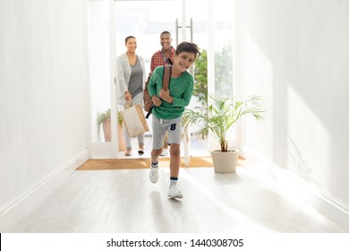 Front view of happy Caucasian family entering their house