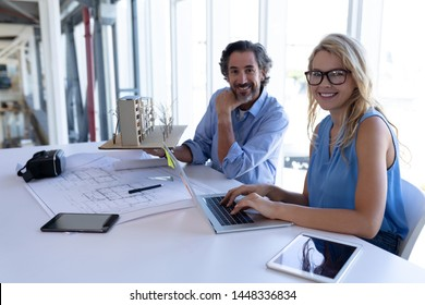 Front view of happy Caucasian male and female architect looking at camera while working table in a modern office. This is a casual creative start-up business office for a diverse team