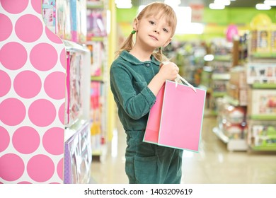 Front view of happy child keeping pink paper bag with new doll and looking at camera in shop. Cute girl posing while choosing and buying toys in big mall. Concept of presents and shopping.