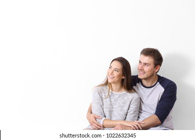 Front view of a happy couple looking at side on a white wall