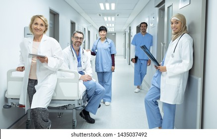 Front view of happy diverse doctors and surgeons looking at camera in the corridor at hospital