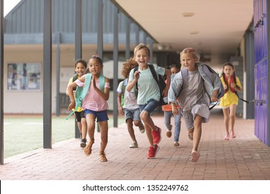 Front view of happy diverse school kids running in corridor at school