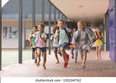 Vue de devant d'heureux élèves de différentes écoles courant dans un couloir à l'école