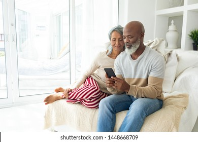 Front view of happy diverse senior couple using a smartphone on sofa in beach house. Authentic Senior Retired Life Concept